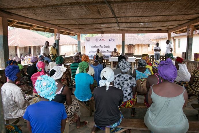 Approximately 45 people wait to receive cash transfers during a Catholic Relief Services distribution in Konia village, Kanema district, in Sierra Leone. / Michael Stulman, CRS