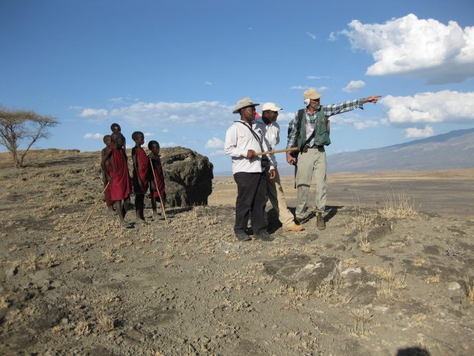 A VDAP team member consults with scientists from the Geological Survey of Tanzania while children observe. / Thomas Casadevall, USGS
