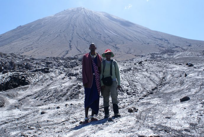 Gari Mayberry (right) with a guide in front of Ol Dionyo Lengai Volcano in January 2009. / Thomas Casadevall, USGS