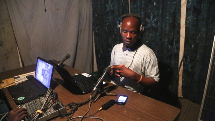 A radio host prepares to go live on an Ebola-related talk show. /Ida Jooste, Internews