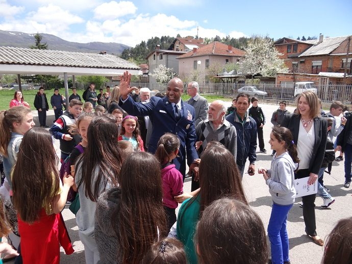 "Students at the ""Bratstvo Edinstvo"" primary school in Macedonia high-five U.S. Air Force Chief Master Sergeant David Cox at its dedication ceremony as an IIEP school. Photo by Macedonian Civic Education Center"
