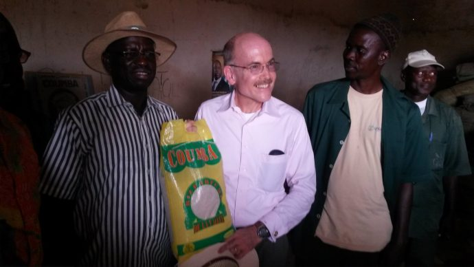 im Zumwalt, U.S. Ambassador to Senegal, stands with Ibrahima Sall, the founder of Coumba Nor Thiam, a medium-sized rice milling firm established in the northern part of Senegal. USAID/Senegal is working with the firm and other enterprises to develop a system to improve smallholder rice farmers' ability to access urban markets. / USAID/Senegal