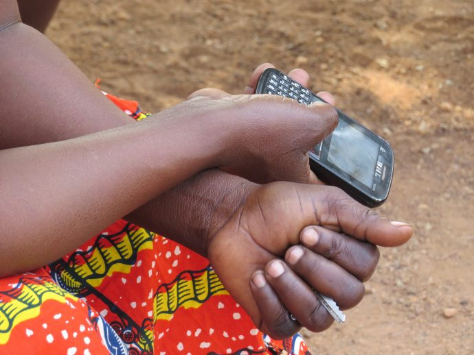 A woman holds a mobile phone in Ghana. /John O'Bryan, USAID