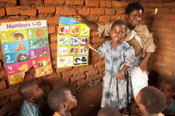 A Malawian schoolgirl reads out loud to her class. USAID is working to improve reading skills in primary school students and create safe spaces for girls to learn. / Amos Gumulira, Feed the Children