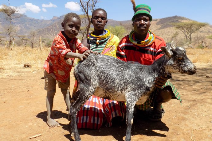 "Livestock owner and her family show off their ""Milk Queen"" goat. / ACDI/VOCA"
