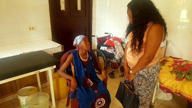 Karoline Nyoka, a program officer with Health Communication Capacity Collaborative, greets and interviews patient Salematou Sylla. / Mariama Keita, USAID