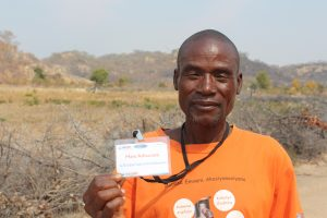 "A man stands ourdoors, holding a badge that reads ""USAID Male Advocate"""