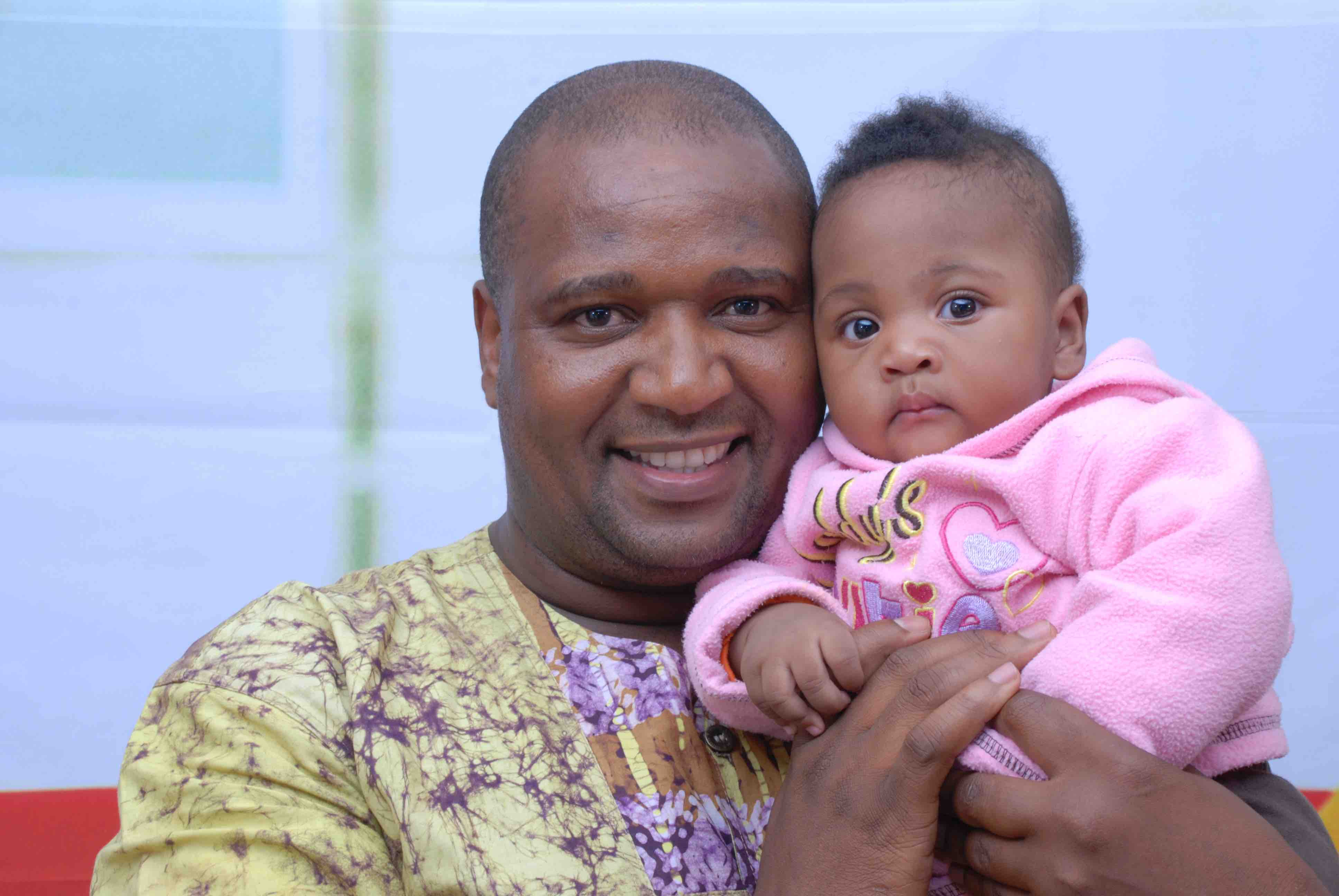 Themba smiles and poses for the cameras with a young baby