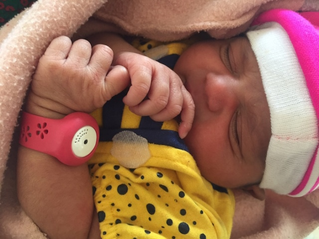 A newborn baby wears the BEMPU Hypothermia Alert device on its wrist
