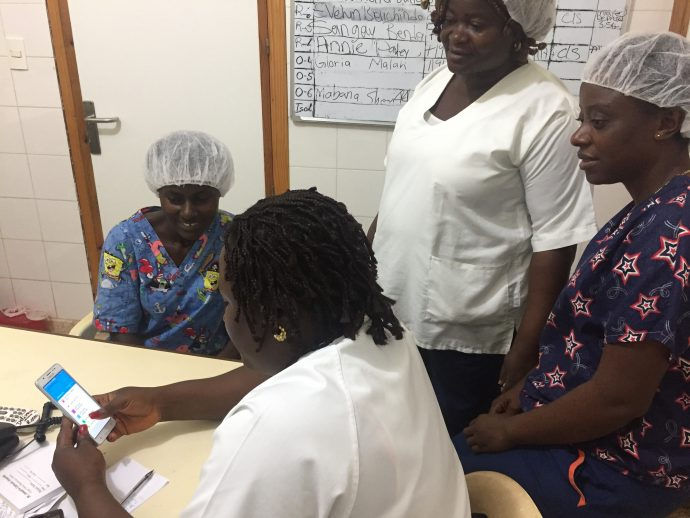 A group of women medical practitioners share a smart phone to look at the app