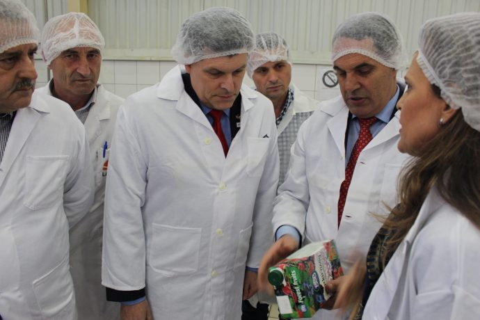 A group of people wearing lab coats and hair nets, examines a product produced in the factory the group is visiting