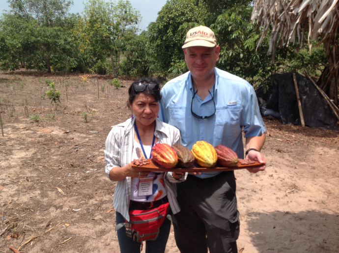 A woman (Irene Chamalla), left, and a man (USAID Peru Mission Director Lawrrence Rubey), right, stand outdoors holding a tray of unprocessed cacao pods