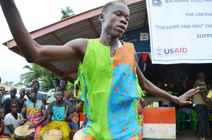 A low angle of a man in a colorful shirt, with his arms out, as if he is dancing