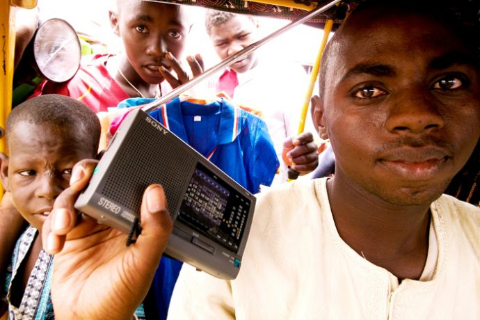 A man in a white t-shirt holds up a small portable radio