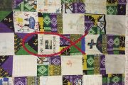 A purple and white patchwork quilt hanging on a wall.