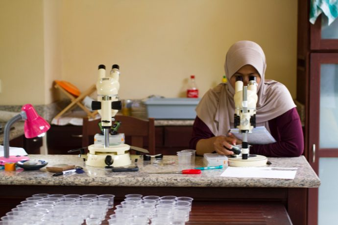 A woman looks into a microscope in a lab