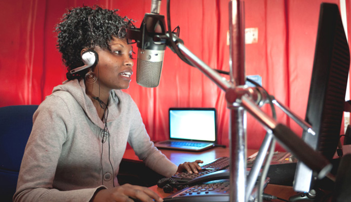 A woman sits in a studio in front of a large broadcasting microphone