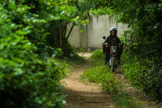 A woman rides a motorbike on a dirt road through a forest