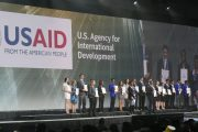A group of young people stand in a row on a stage holding certificates