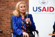 A woman sits with a microphone in front of a USAID banner