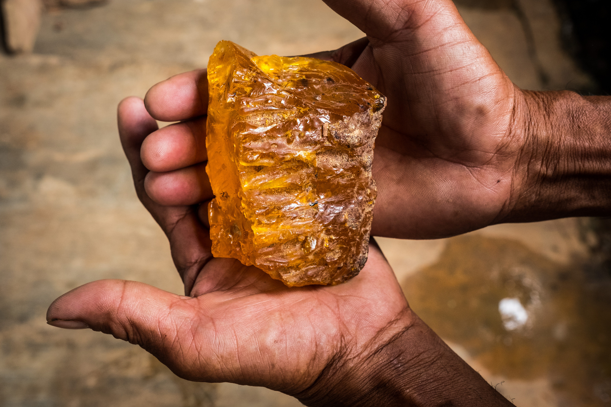 Two hands holding a chunk of resin