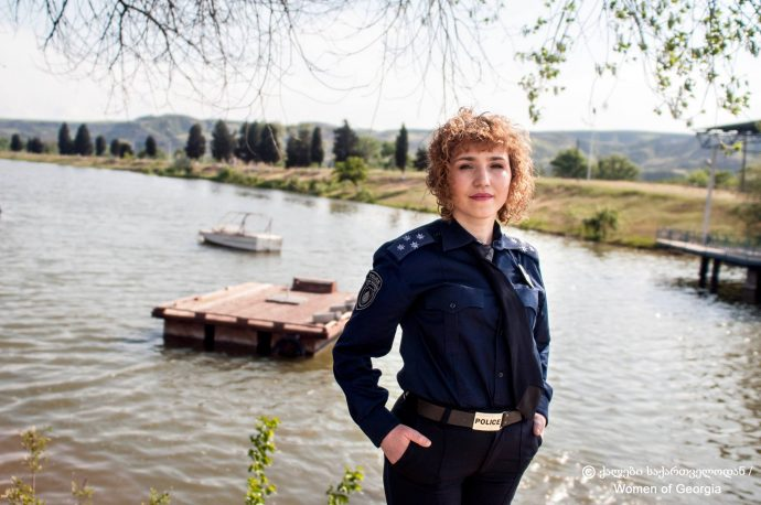 A woman wearing a police uniform stands in front of a dock on a lake