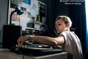 A woman works with a DJ's turntable